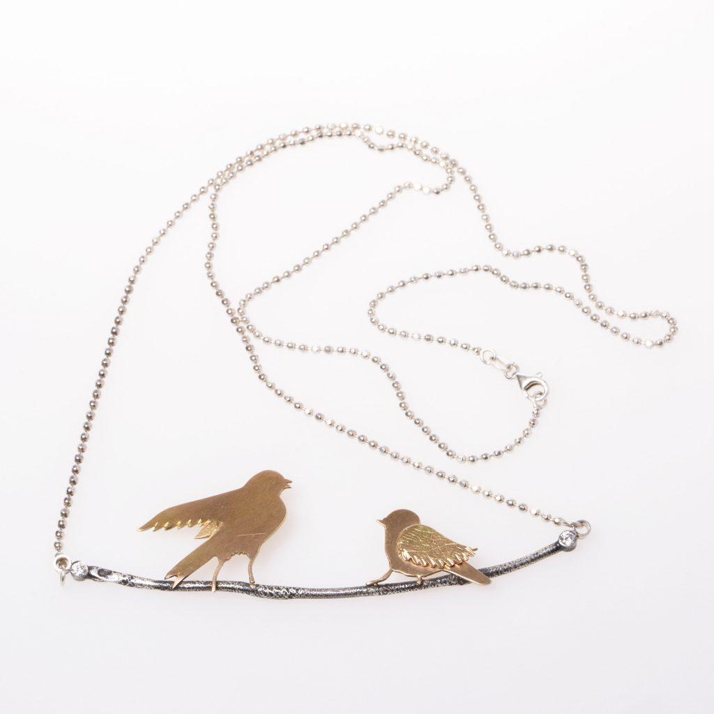Halsband med guldfåglar på silverkvist.